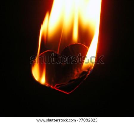 Burning paper heart over black background - stock photo