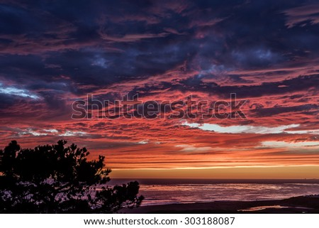 Burning red sun, thunderheads, pending storm, painted sky, and reflective sea at sunset, on (Big Sur Coast) Moonstone Beach, with people in the distance. California Central Coast, near Cambria CA. - stock photo