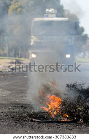 Burning rubber tyres in the streets in South Africa with police riot vehicle in the background - stock photo