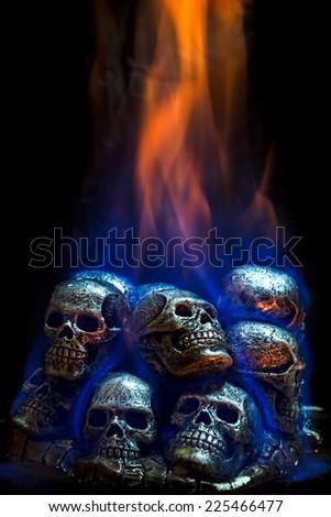 Burning skulls on black background - stock photo