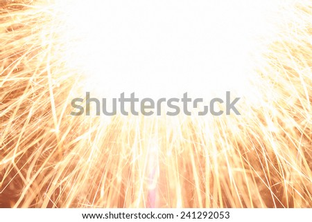 Burning sparkler in front of a dark background. - stock photo