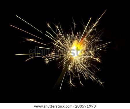 Burning sparkler isolated on black background - stock photo