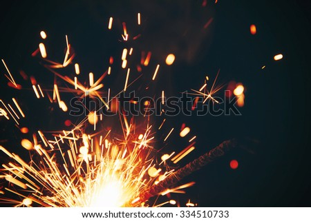 burning sparkler on a dark background - stock photo