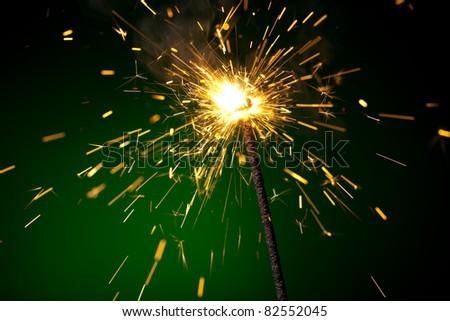 burning sparkler on green - stock photo