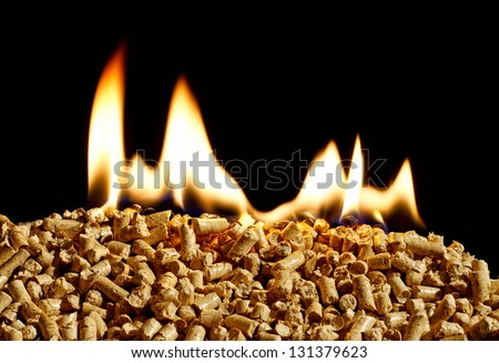 burning wood chip pellets a renewable source of energy becoming popular as a green environmentally friendly fuel for stoves which provide household heating - stock photo