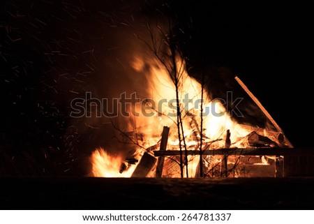 Burning wood house. Ruins. Dark night. Light sparkles flying around the trees  - stock photo