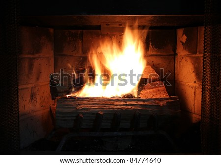 Burning wood in a brick fire place. - stock photo