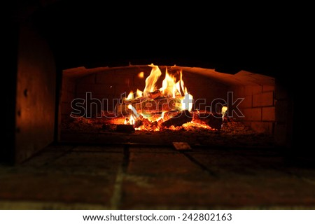 Burning wood in an oven at the kitchen - stock photo