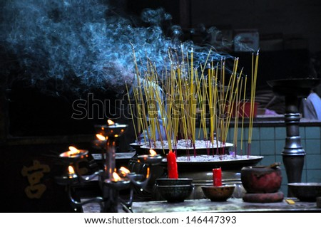 Burning yellow incense sticks in a pot. Ho Chi Minh city, Vietnam - stock photo