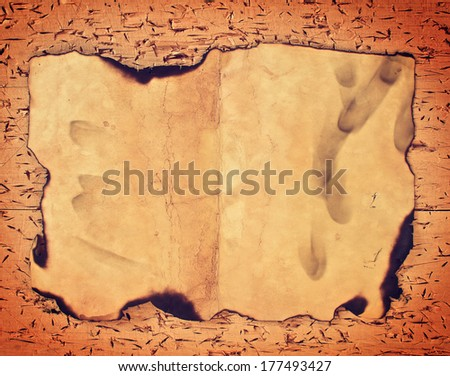 Burnt old paper on wooden grungy background - stock photo