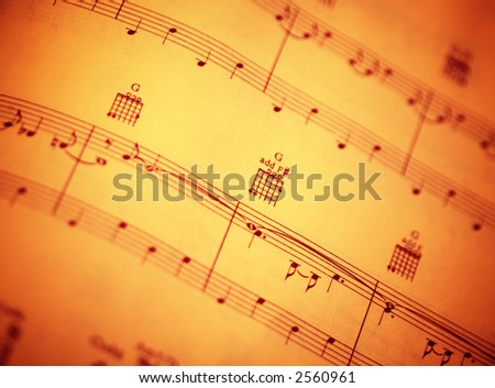 Burnt orange sheet music with guitar chords - stock photo