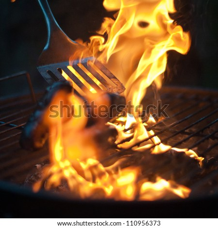 Burnt Sausages being flipped in a BBQ flame - stock photo
