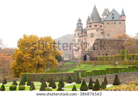 Burresheim Castle with triangle shaped topiary green trees in old ornamental garden in autumn, Germany. Outdoors horizontal image - stock photo