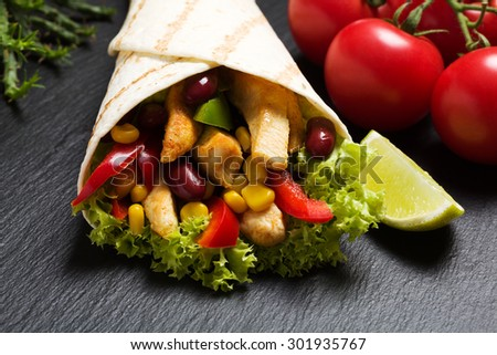 Burritos wraps with chicken, beans and vegetables on wood board - stock photo