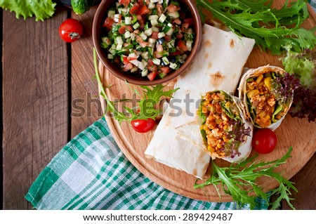 Burritos wraps with minced beef and vegetables on a wooden background. Top view - stock photo