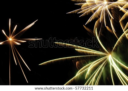Bursts of fireworks with white-hot cores and reddish-orange, greenish, and white streaks with feathery motion blur - stock photo