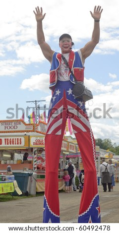 BURTON, OH - SEPT 5: A clown on stilts waves a greeting at the 188th annual Great Geauga County Fair on September 5, 2010 in Burton, Ohio. - stock photo