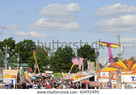 BURTON, OH - SEPT 5: Crowds throng the concessions, with amusement rides in background, at the 188th annual Great Geauga County Fair on September 5, 2010 in Burton, Ohio. - stock photo