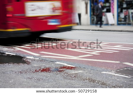 Bus lane in London with red bus crossing over the sign - stock photo
