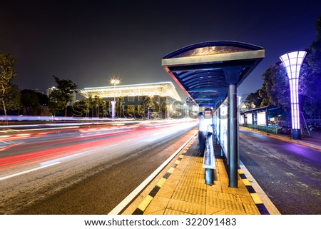 bus station next to a road at night with neon light - stock photo