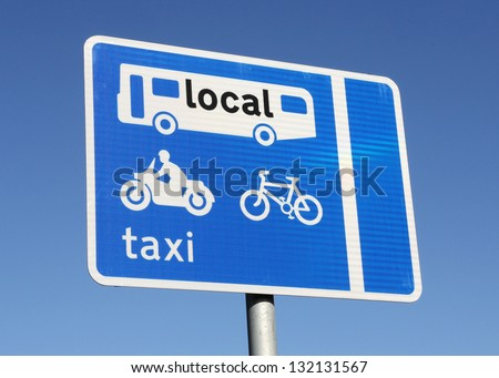 Bus, taxi, motor bike and bicycle reserved lane sign on a busy road. - stock photo
