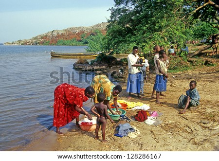 BUSAGAZI, BUIKWE REGION, UGANDA - JULY 31: An unidentified family washes clothes on the banks of Lake Victoria on July 31, 2004 in Busagazi village. Uganda is one of the poorest nations in the world. - stock photo