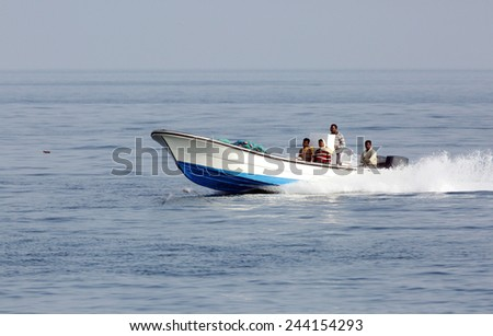 BUSAITEEN, BAHRAIN-SEPTEMBER 27: Early morning fisher men moving in the sea on speedboat with fishing nets at Busaiteen sea coast on September 27, 2014, Bahrain - stock photo
