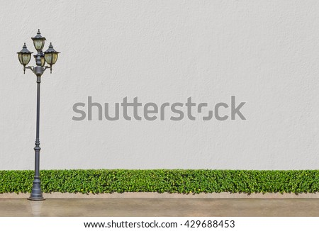 bush fence and concrete wall : street electric lamp post at green bush fence and white concrete wall and brown concrete background - stock photo