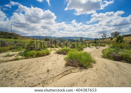 Bushes grow in the bottom of a dry creekbed during drought in American southwest. - stock photo