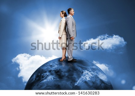 Busines people standing back to back on top of the world in blue sky with sun - stock photo
