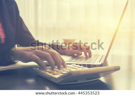 business, accounting,investment,Businessman analyzing investment charts with calculator laptop calculate with technology in office,selective focus,vintage color - stock photo