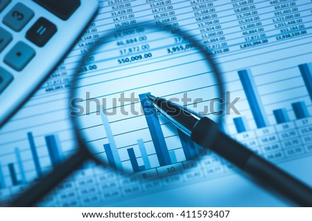 Business accounting spreadsheet with calculator and pen through magnifying glass in business blue, close up macro - stock photo