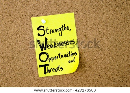 Business Acronym SWOT Strengths, Weaknesses, Opportunities and Threats written on yellow paper note pinned on cork board with white thumbtack, copy space available - stock photo