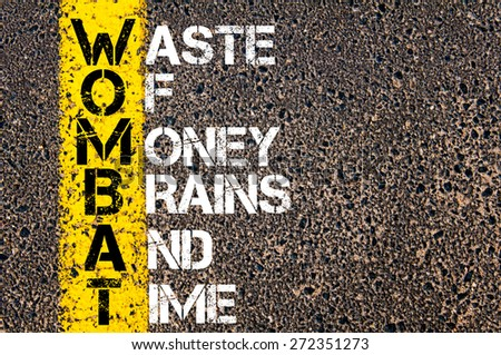 Business Acronym WOMBAT as WASTE OF MONEY, BRAINS AND TIME. Yellow paint line on the road against asphalt background. Conceptual image - stock photo