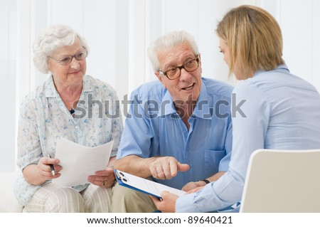 Business agent planning with a retired couple their future investments - stock photo