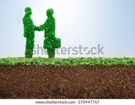 Business agreement concept with grass growing in shape of two businessmen shaking hangs  - stock photo