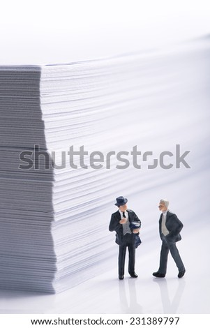 Business agreement. Two businessmen negotiating beside an office paper stack - stock photo