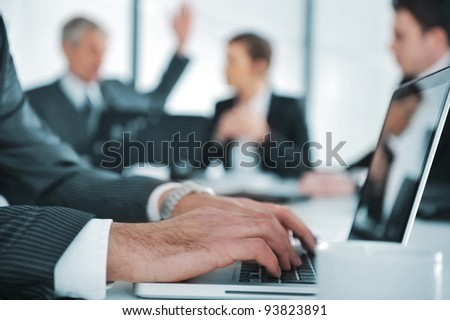 Business ambiance, typing report on laptop during the meeting - stock photo