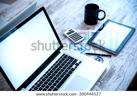 Business Analytics on a wooden Desk with a Tablet PC and a Laptop.