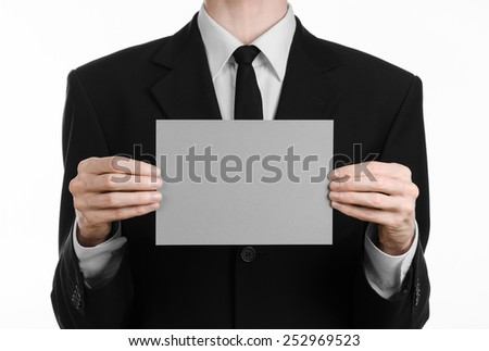 Business and advertising topic: Man in black suit holding a gray blank card in hand isolated on white background in studio - stock photo