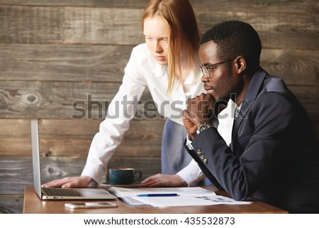 Business and career concept. Teamwork and cooperation: African man in formal suit and Caucasian woman in white shirt videoconferencing and negotiating with their partners using generic laptop - stock photo
