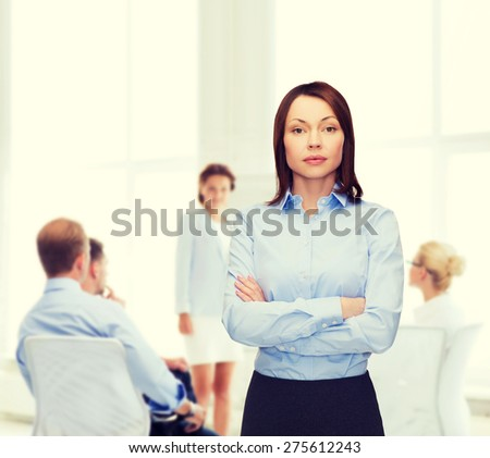 business and education concept - friendly young businesswoman with crossed arms at office - stock photo