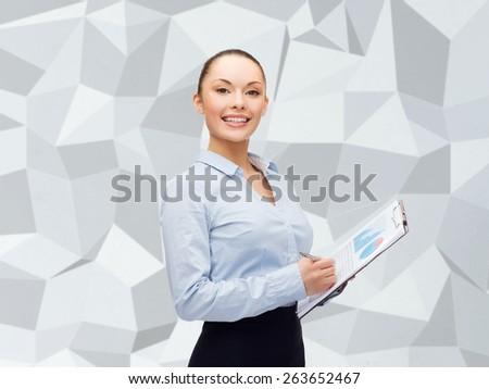 business and education concept - friendly young smiling businesswoman with clipboard and pen over gray graphic low poly background - stock photo