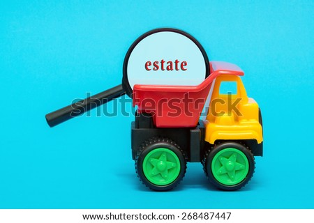 Business and finance concept. Toy lorry carrying a magnifying glass looking for word ESTATE on blue background - stock photo