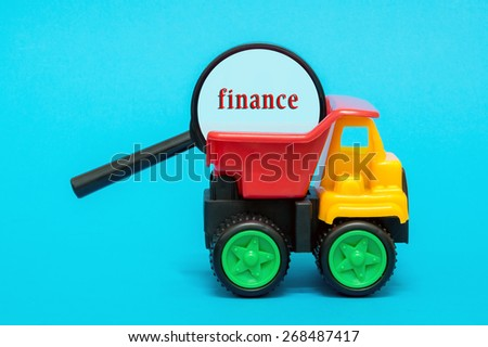 Business and finance concept. Toy lorry carrying a magnifying glass looking for word FINANCE on blue background - stock photo