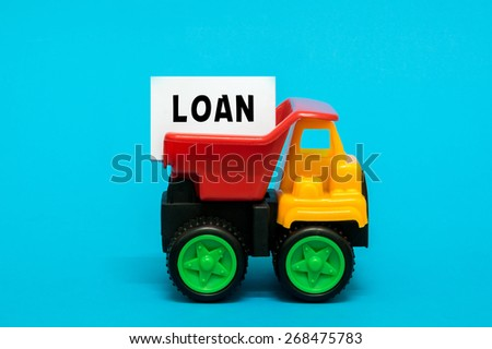 Business and finance concept. Toy lorry transporting a LOAN note on blue background. - stock photo