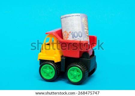 Business and finance concept. Toy lorry transporting a Malaysia Ringgit hundred dollar note on blue background.  - stock photo