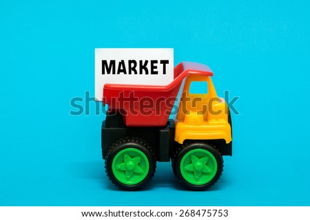 Business and finance concept. Toy lorry transporting a MARKET note on blue background. - stock photo