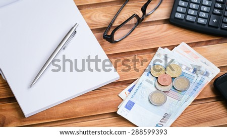 Business and financial objects on a wooden surface - Euro banknotes and coins, an open notepad, glasses and a calculator. - stock photo