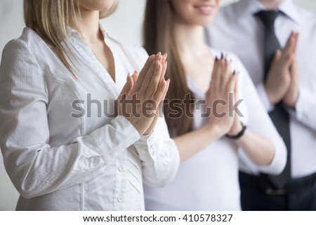 Business and healthy lifestyle concept. Close-up of young office workers standing in yoga pose at workplace. Smiling business people relaxing with arms folded in Prayer gesture on break time - stock photo
